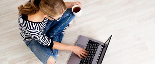 A picture of a woman holding a cup of coffee and sitting on the floor with a laptop.
