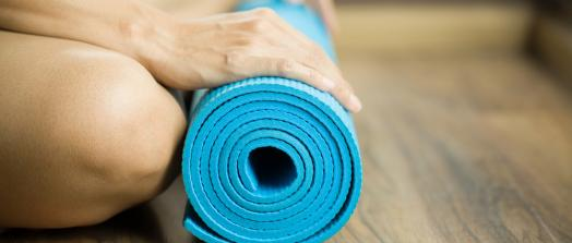 A picture of a rolled gym mat on the floor at the feet of a person.